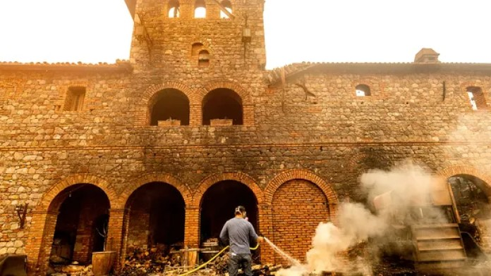 Cellar worker Jose Juan Perez sprays water on burning debris at Castello di Amorosa, Monday, Sept. 28, 2020, in Calistoga, Calif., which was damaged in the Glass Fire.