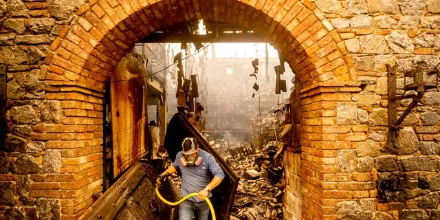 Cellar worker Jose Juan Perez extinguishes hotspots at Castello di Amorosa, Monday, Sept. 28, 2020, in Calistoga, Calif., which was damaged in the Glass Fire.