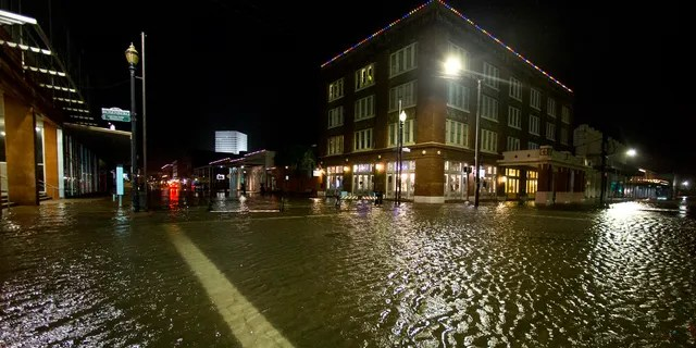 Water rises from the storm surge of Tropical Storm Beta in The Strand as the storm moves toward landfall late Monday, Sept. 21, 2020, in Galveston, Texas.