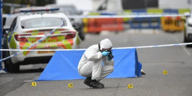 A police forensic officer photographed in Birmingham after several people were killed in the city center on Sunday.  (AP / PA)