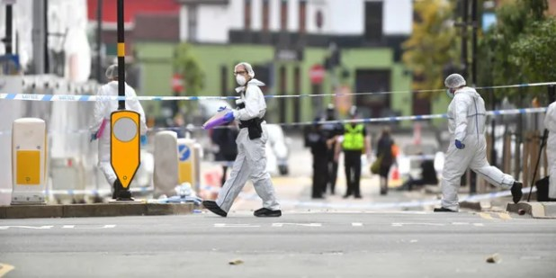 Police forensic officers investigate one of the stabbing scenes.  (AP / PA)