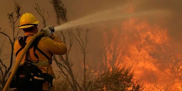 Jesse Vasquez, of the San Bernardino County Fire Department, hoses down hot spots from the Bobcat Fire on Saturday, Sept. 19, 2020, in Valyermo, Calif.