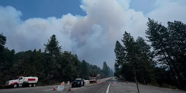 Smoke from the Creek Fire billows in the sky at a road closure Monday, Sept. 7, 2020, in Shaver Lake, Calif.