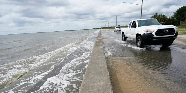 Waters from the Guld of Mexico poor onto a local road, Monday, Sept. 14, 2020, in Waveland, Miss.