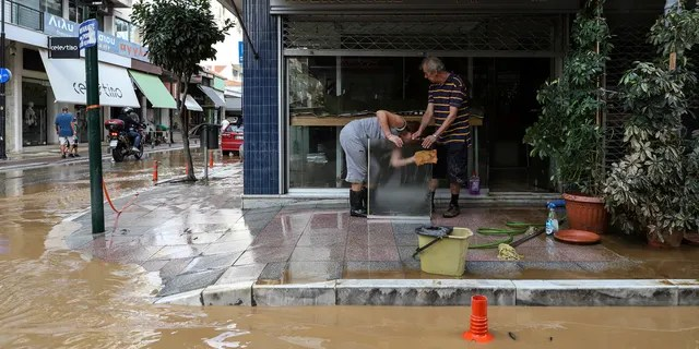 Residents clean a sheet of glass next to a flooded street after a storm in the town of Karditsa, Saturday, September 19, 2020.