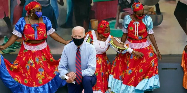 Democratic presidential candidate former Vice President Joe Biden poses fora. Photo with dancers as he visits Little Haiti Cultural Complex, Monday, Oct. 5, 2020, in Miami. (AP Photo/Andrew Harnik)