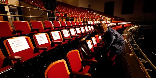 A member of the production staff puts labels on seats in an effort to keep seats socially distanced ahead of the vice presidential debate (AP Photo/Julio Cortez)