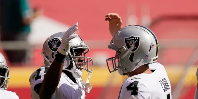 Las Vegas Raiders wide receiver Nelson Agholor, left, celebrates with quarterback Derek Carr after catching a 59-yard touchdown pass during the first half of a game against the Kansas City Chiefs, Sunday, Oct. 11, 2020, in Kansas City.