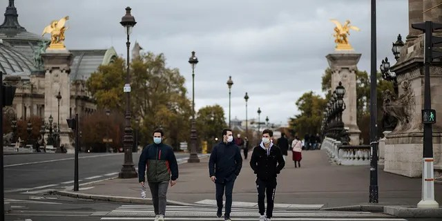 People wearing masks walk around the Invalides district in Paris, Sunday, October 25, 2020 (AP Photo / Lewis Joly)