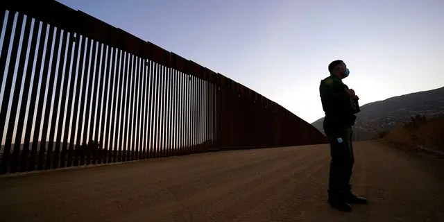 Border Patrol agent Justin Castrejon speaks in front of newly replaced border wall sections Thursday, Sept. 24, 2020, near Tecate, Calif. (AP Photo/Gregory Bull)