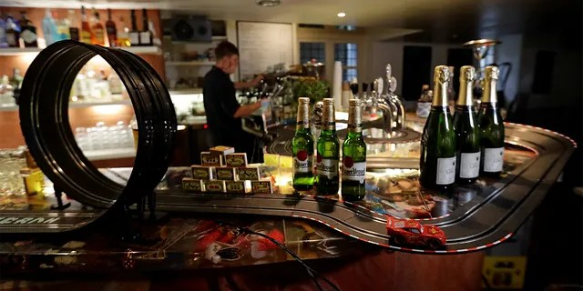 A bartender prepares a drink after turning a bar into an electric car track.  (REUTERS / David W Cerny)