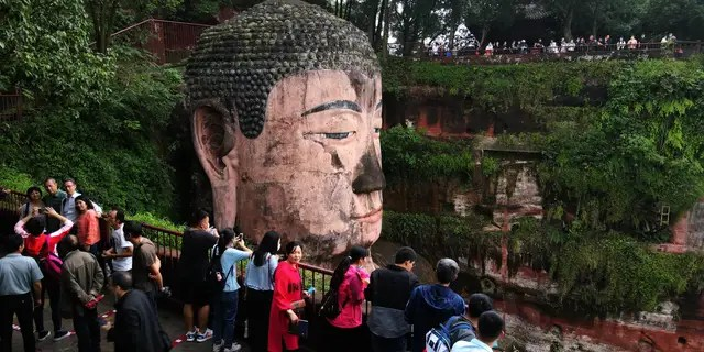 Tourists visit the Leshan Giant Buddha, a UNESCO World Heritage Site, on the first day of the eight-day national holiday on October 1.  (Liu Zhongjun / China News Service via Getty Images)