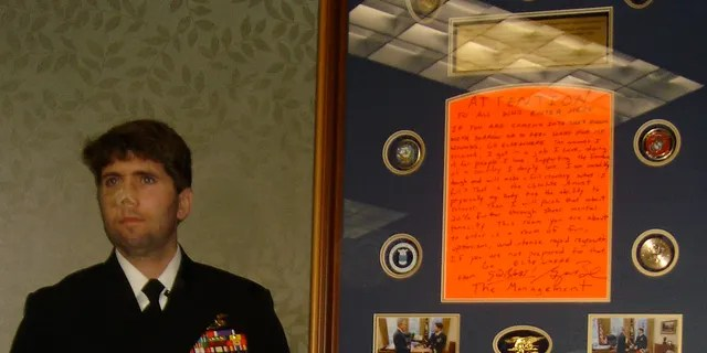Jason Redman, a former Navy SEAL, stands beside the sign he once placed on his door at Walter Reed.