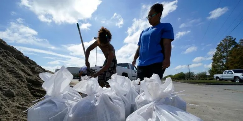 Stephanie Verrett and Jodie Jones fill sandbags to protect their home in anticipation of Hurricane Delta, expected to arrive along the Gulf Coast later this week, in Houma, La., Wednesday, Oct. 7, 2020.