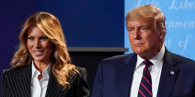 In this Sept. 29, 2020, file photo, President Donald Trump and first lady Melania Trump hold hands on stage after the first presidential debate at Case Western University and Cleveland Clinic, in Cleveland, Ohio. (AP Photo/Julio Cortez, File)