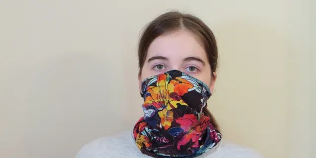 Emma Fischer, study co-author and student at Duke University, dons a neck gaiter. Study co-author Warren S. Warren says this neck gaiter is slightly stretchy and opaque when worn, but single layer and thin enough to see a light through it.
