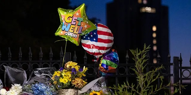 Flowers and balloons left by supporters of President Donald Trump at the entrance to Walter Reed National Military Medical Center (background) in Bethesda, Md., Sunday, Oct. 4, 2020. Trump was admitted to the hospital after contracting the coronavirus. (AP Photo/Cliff Owen)