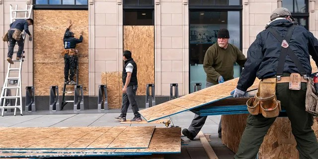 Ahead of the presidential election, workers with Baguer Construction LLC board up a Walgreens on U Street NW, Friday, Oct. 30, 2020, in Washington. The site manager said they had been hired to put protective coverings on several Walgreens throughout the city. (AP Photo/Jacquelyn Martin)