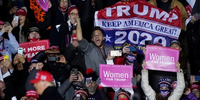 Supporters cheer as President Donald Trump exits a campaign event early Tuesday, Nov. 3, 2020, in Grand Rapids, Mich. (AP Photo/Carlos Osorio)