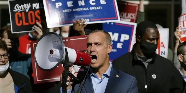 President Donald Trump's campaign advisor Corey Lewandowski, center, speaks about a court order obtained to grant more access to vote counting operations at the Pennsylvania Convention Center, Thursday, Nov. 5, 2020, in Philadelphia, following Tuesday's election. (AP Photo/Matt Slocum)