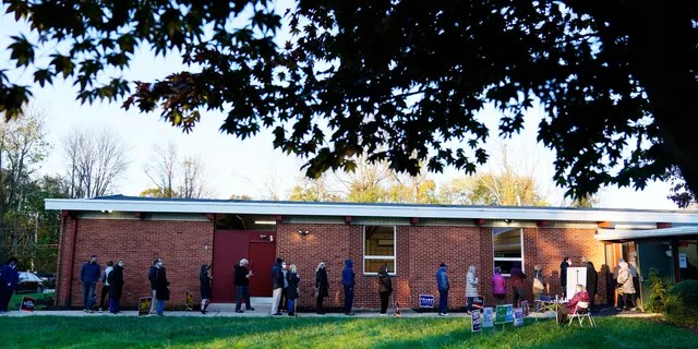 People line up outside a polling place to vote in the 2020 general election Tuesday, Nov. 3, 2020, in Springfield, Pa. (AP Photo/Matt Slocum)