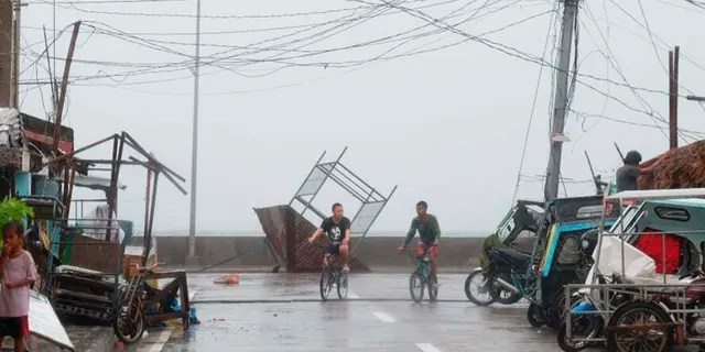 Residents walk past a toppled structure as waves batter the coast of Sorsogon province, central Philippines as Typhoon Goni hits the country on Sunday, Nov. 1, 2020. (Associated Press)