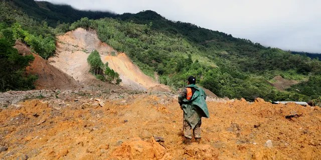 A member of a search and rescue team searches for survivors following destruction caused by a massive rain-fed landslide in the village of Queja, Guatemala, Saturday, November 7, 2020, in the aftermath of tropical storm Eta.
