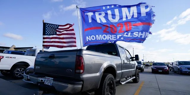 Flags fly over a pickup truck outside a President Donald Trump campaign rally at Dubuque Regional Airport, Sunday, Nov. 1, 2020, in Dubuque, Iowa.