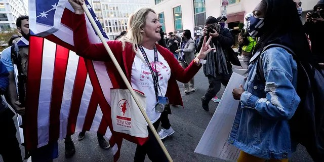A woman gestures as she argues with a counter-protester. The counter-protester was seen on video running up behind the woman and punching her in the back of the head before running away. (AP Photo/Julio Cortez)