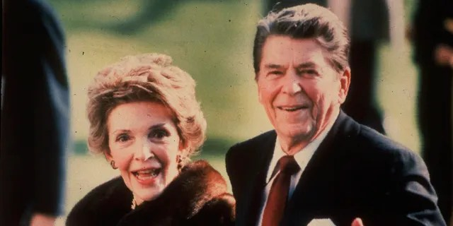 This December 1986, file photo shows first lady Nancy Reagan holding the Reagans' pet Rex, a King Charles spaniel, as she and President Reagan walk on the White House South lawn. (AP Photo/Dennis Cook)