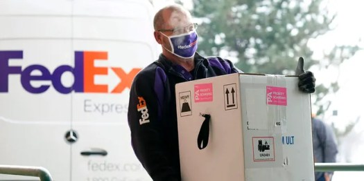 A FedEx driver carries a box to Colorado Gov. Jared Polis so he can sign for the delivery of the state's first shipment of COVID-19 vaccine at the Colorado Department of Public Health and Environment, early Monday, Dec. 14, 2020, in Denver. (AP Photo/David Zalubowski)