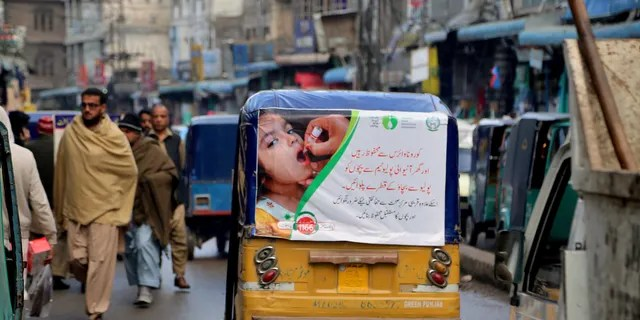 An auto rickshaw with a poster advertising a polio campaign drives through a market in Peshawar, Pakistan. Pakistan, Afghanistan and Nigeria are the only countries in the world where polio is still endemic. Lack of trust in vaccinations is one of many obstacles that will face public health officials in poor and developing countries as they seek to vaccinate millions of people against COVID-19. (AP Photo/Muhammad Sajjad)