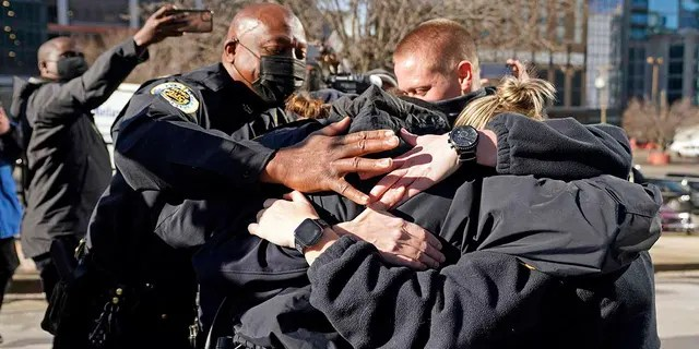 Nashville Police Chief John Drake, left, joins a group of police officers as they embrace after speaking at a news conference Sunday, Dec. 27, 2020, in Nashville, Tenn. The officers are part of a group of officers credited with evacuating people before an explosion took place in downtown Nashville early Christmas morning. (AP Photo/Mark Humphrey)