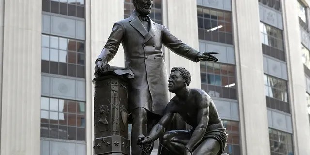 FILE - In this June 25, 2020, file photo, a statue that depicts a freed slave kneeling at President Abraham Lincoln's feet rests on a pedestal in Boston. On Tuesday, Dec. 29, the statue that drew objections amid a national reckoning with racial injustice was removed from its perch. (AP Photo/Steven Senne, File)