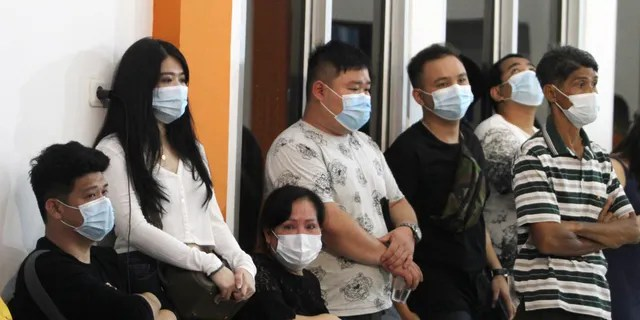 People await news from relatives aboard a Sriwijaya Air passenger plane that lost contact with air traffic controllers after take off from Soepadio International Airport in Pontianak, West Kalimantan, Indonesia, Saturday January 9, 2021 (AP Photo / Helmansyah)