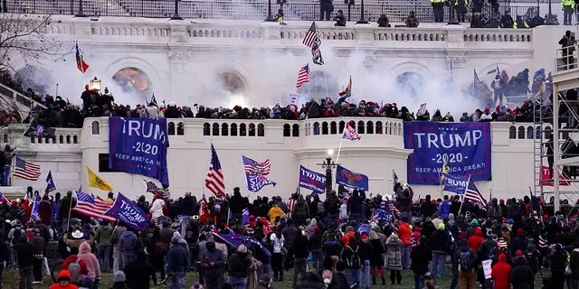 In this Wednesday, Jan. 6, 2021, file photo, violent protesters storm the Capitol in Washington, D.C. Federal prosecutors say a retired Air Force officer who was part of the mob that stormed the U.S. Capitol was arrested Sunday, Jan. 10, 2021, in Texas. (AP Photo/John Minchillo, File)