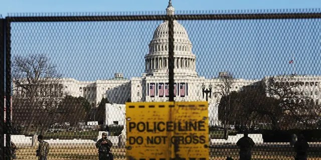 National Guardsmen are seen Wednesday, Jan. 13, 2021, on a fence erected to reinforce security at the Capitol in Washington. (AP Photo/Shafkat Anowar)