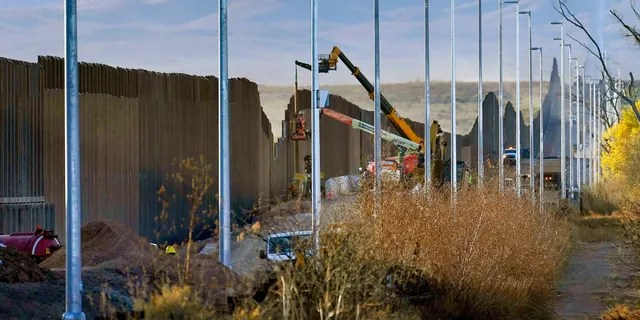 "FILE - Crews construct a section of border wall in San Bernardino National Wildlife Refuge, Tuesday, Dec. 8, 2020, in Douglas, Ariz. President Biden on Wednesday ordered a ""pause"" on all wall construction within a week. (AP Photo/Matt York)"