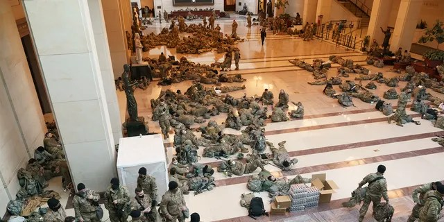 Hundreds of National Guard troops gather inside the Capitol to reinforce security on Wednesday, Jan. 13, 2021, as the House voted to impeach President Trump for inciting a mob that stormed the building last week. (AP Photo/J. Scott Applewhite)