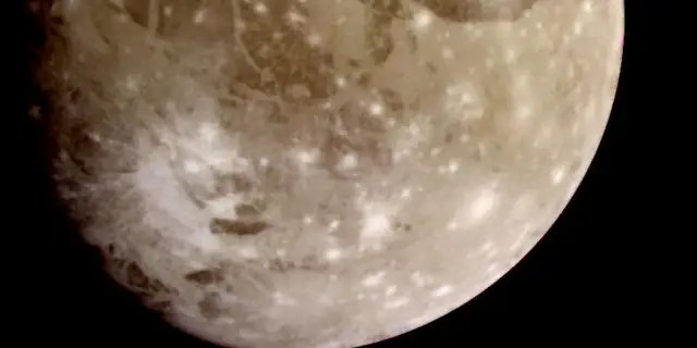 Natural color view of Ganymede from the Galileo spacecraft during its first encounter with the satellite. North is to the top of the picture and the sun illuminates the surface from the right. The dark areas are the older, more heavily cratered regions and the light areas are younger, tectonically deformed regions. (NASA/JPL)