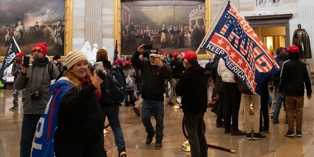 Jenny Cudd, of Midland, Texas, is seen inside the US Capitol holding her phone and draped with a Trump flag. (SAUL LOEB/AFP via Getty Images)