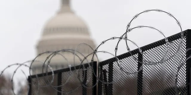 """The U.S. Capitol is seen behind the razor fence around the U.S. Capitol on Feb. 18. U.S. Fencing around the area will be errected ahead of Saturday's """"Justice for J6"""" rally in supporters of those charged inthe deadly Jan. 6 riot inthe Capitol. (AP Photo/Manuel Balce Ceneta)"""