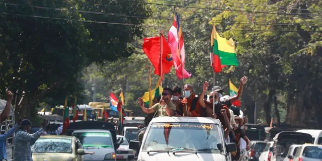 Buddhist religious and military flags are waved by supporters, with a vehicle carrying Buddhist monks on Monday, February 1, 2021 in Yangon, Burma.  Burma's military has announced that it will hold a new election at the end of a year's emergency that it announced on Monday when it seized control of the country and reportedly detained leader Aung San Suu Kyi Was.  (AP Photo / Thein Zaw)