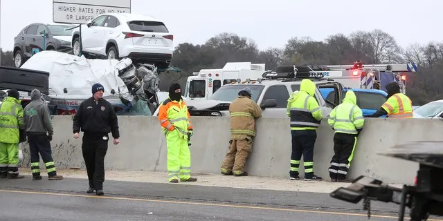 First responders work the scene of a fatal crash on I-35 near downtown Fort Worth on Thursday, Feb. 11, 2021. Police say at least six people were killed and dozens injured in a massive crash involving 75 to 100 vehicles on an icy Texas interstate. (Amanda McCoy /Star-Telegram via AP)