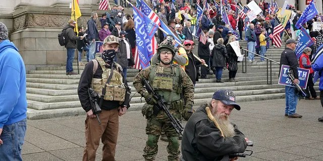 FILE - In this Jan. 6, 2021, file photo at the Capitol in Olympia, Wash., two men stand armed with guns at a protest supporting President Donald Trump and against the counting of electoral votes in Washington, DC, affirming President-elect Joe Biden's victory.  (AP Photo/Ted S. Warren, File)