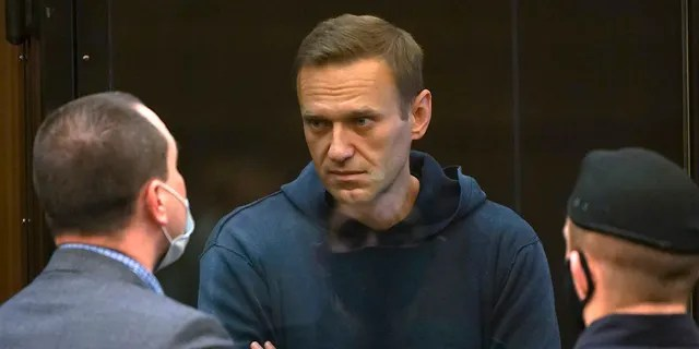 In this handout photo provided by the Moscow City Court, Russian opposition leader Alexey Navalny spoke to one of his attorneys while standing in a cage during the hearing of a motion from the Russian prison service to change Navalny's suspended sentence from the 2014 convict Was.  An actual prison sentence in Moscow City Court in Moscow, Russia, Tuesday, February 2, 2021.  (Via Moscow City Court)