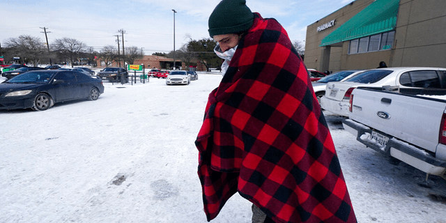 Cody Jennings uses a blanket to keep warm outside a grocery store on Tuesday, February 16, 2021 in Dallas.
