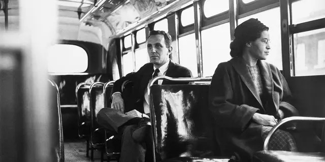 On December 21, 1956, American civil rights activist Rosa Parks sits in front of a bus in Montgomery, Alabama, after the city bus system ruled illegal segregation.