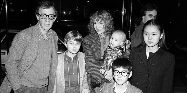 American comedian, actor, and film director Woody Allen (left) and his partner, actress Mia Farrow pose under an awning with their children, from left, Misha, Dylan (in Farrow's arms), Fletcher, and Soon Yi, New York, New York, 1986. Soon-Yi later married Allen. The man in background is unidentified.