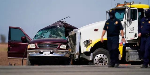 Law enforcement officers work at the scene of a deadly crash in Holtville, Calif., on Tuesday, March 2, 2021. Authorities say a semi-truck crashed into an SUV carrying 25 people on a Southern California highway, killing at least 13 people. (AP Photo/Gregory Bull)